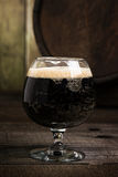 Russian Imperial Stout in snifter glass on wood background and b Stock Photo