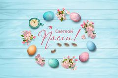 Easter Top View Background. Russian inscription Happy Easter inside decorative frame. Circular border consisting of spring flowers, eggs, feathers, candle on Stock Photo