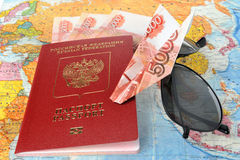 Russian international passport, money, sunglasses and origami pl. Ane made from money on the world map Royalty Free Stock Images