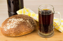 Russian kvass in bottle and mug, round loaf of bread Stock Photos