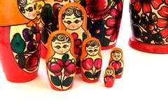 Russian Matryoshka Nesting Dolls. A set of unique Russian Matryoshka nesting dolls with colorful reds and orange decorate a table top Royalty Free Stock Images