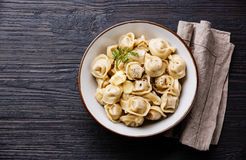 Russian meat Dumplings Pelmeni. In bowl serving size on burned black wooden background Royalty Free Stock Photo