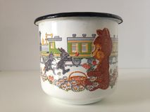 Russian Metal Cup. Russian Metal Cup with Picture of Green Electric Train, Wolf Running after Hare, and Bear Eating Berries Stock Images