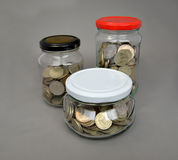 The Russian metallic currency is in glass jars on a gray backgro Stock Photos