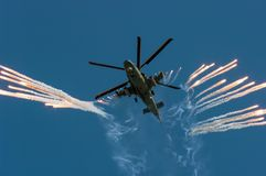Russian military helicopter Ka-52 fires off heat decoy on air-show. Military helicopter Ka-52 of russian airforce are flying and fires off heat decoy royalty free stock images