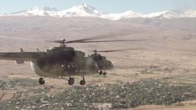 Russian military helicopters fly against the snow-capped mountains. Russian military helicopters fly over the village on the background of snow-capped mountains stock video footage