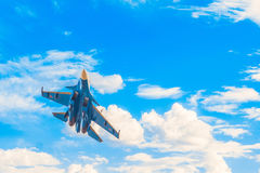 Russian military jet fighter flying in the blue cloudy sky. Background with copy space Royalty Free Stock Photo