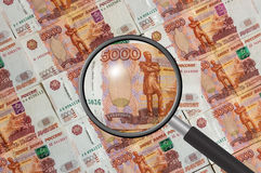Russian money background with magnifying glass Stock Photos