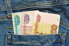Russian money in jeans pocket. Some russian national currency paper notes - rubles, approximately 25 US dollars in pocket of old worn blue jeans. Poverty concept royalty free stock image