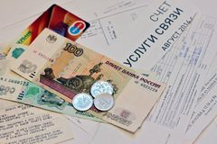 Russian money - notes and coins, and plastic card payment on receipts of utility bills Royalty Free Stock Image