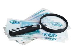 Russian money roubles and magnifying glass. Russian money of the bill on thousand of roubles and magnifying glass on white background Royalty Free Stock Images