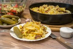 Russian national cuisine: fried potatoes with pickled cucumber, garlic. stock photos