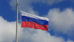 Russian national flag waving on flagpole in blue sky stock footage