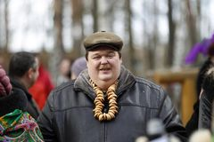 Russian national holiday Maslyanitsa.Tolsty male with a bagel stock image
