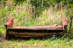 Old broken junk sofa in the woods. Russian nature-lovers often don`t dispose the wastes by the proper way, therefore, the favorite recreation areas are Stock Images
