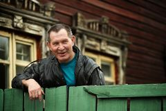 Russian old man look out fence. Old house royalty free stock photos