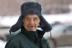 Russian old man in winter hat smiles royalty free stock images