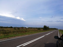 Russian open spaces in anticipation of the storm. Ivashkovo, Moscow Region, Russia – August 19, 2016: Road beetwen villages. On the left in the distance is Stock Photography