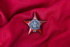 Russian Order of the Red Star on red background. Russian Order of the Red Star on the background of red cloth stock photos