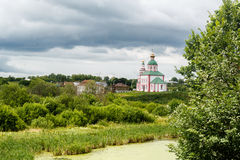 Of the Russian Orthodox Church near the river on a background of clouds Stock Photo