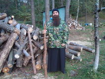 Russian Orthodox priest with a log on the construction of the temple. Royalty Free Stock Images