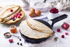 Russian pancake blini. Maslenitsa festival meal. Russian pancake blini with berry, honey, jam on white wooden background, ingredient for making Royalty Free Stock Images
