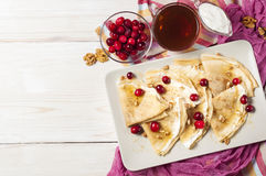 Russian pancake blini on white wooden background. Shrovetide Maslenitsa festival meal. Russian pancake blini with cranberry, honey, fresh cream and walnuts on royalty free stock photos