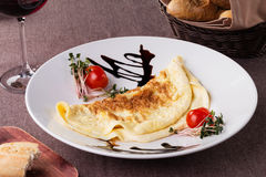 Russian pancake folded on a white plate on the dark background Stock Images