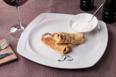 Russian pancake folded on a white plate on the dark background Stock Photo