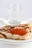 Russian pancake with red caviar and vodka Stock Photos