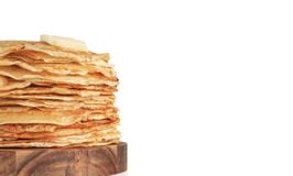 Russian pancakes blini on black with copy space. Stack of traditional russian pancakes blini isolated on white background with copy space. Homemade russian thin stock image