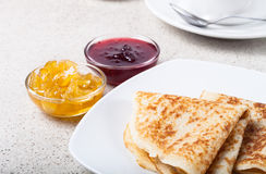 Russian pancakes - blini with cup of tea, jam and sour cream Royalty Free Stock Image