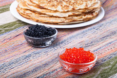 Russian pancakes - blini with red and black caviar stock photo