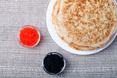 Russian pancakes - blini with red and black caviar royalty free stock image