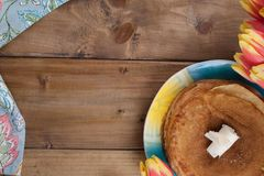 Russian pancakes with butter on a wooden background. A bouquet of fresh spring tulips and traditional Russian food. Free space for royalty free stock photography