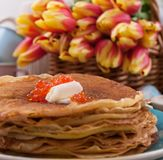 Russian pancakes with butter on a wooden background. A bouquet of fresh spring tulips and traditional Russian food. Free space for stock photo