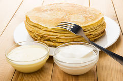Russian pancakes in glass dish and condensed milk, sour cream Royalty Free Stock Photography