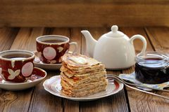 Russian pancakes in heap with jam and black tea Stock Photo