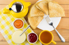 Russian pancakes in plate, jam, condensed milk, teapot and tea Stock Photo