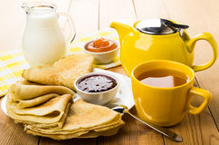 Russian pancakes in plate, jam, jug milk and tea Stock Photography