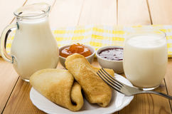 Russian pancakes in plate, milk, fork and bowls with jam Stock Photography