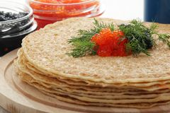 Russian pancakes with red and black caviar. Traditional Russian pancakes with red and black caviar for Maslenitsa celebration stock photo