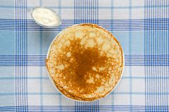 Russian pancakes with sour cream on checker tablecloth. Overhead food shots stock photos