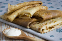 The Russian pancakes with sour cream. The Russian traditional dish, the main thing during Shrovetide, a symbol of spring and the sun Stock Photos