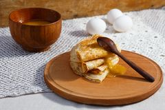 Russian pancakes with wooden spoons, honey Stock Photo