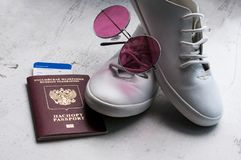 Russian passport with a boarding pass for the plane, white sports shoes and pink sunglasses. Travel concept Selective focus. stock photo