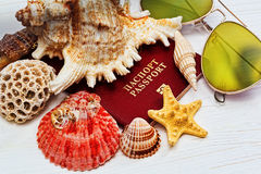 Russian passport covered bt sea shells. Russian passport covered by sea shells and starfish and sunglasses on the wooden desk stock photos