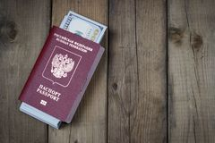 Russian passport with dollars inside on wooden background, concept of immigration stock photo