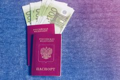 Russian passport with an embedded Euro currency on a blue background. The Russian passport with an embedded Euro currency on a blue background Royalty Free Stock Image