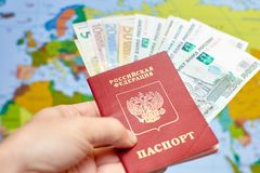 Russian passport with euro banknotes and rubles on the background of the world map stock photo